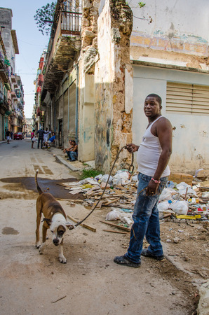 vieja: HAVANA - CUBA JUNE 19, 2016: Man walks his dog along the streets of deteriorating homes in the La Habana Vieja neighborhood. Editorial