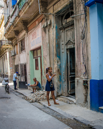 vieja: Havana, Cuba, June 19, 2016 - A young woman checks her cell phone for messages outside her home, one of thousands of deteriorating and decaying buildings in La Habana Vieja.