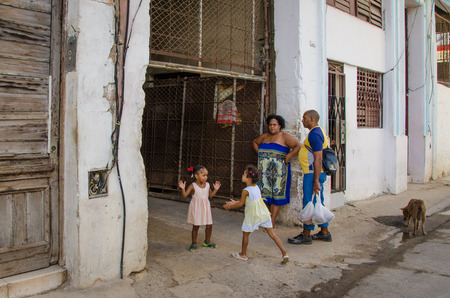 habana: Havana, Cuba, June 19, 2016 - Two girls are playing a clapping game in front of their home, one of thousands of deteriorating and decaying buildings in La Habana Vieja.