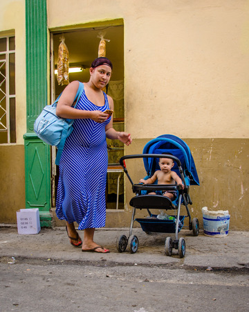 habana: HAVANA - CUBA JUNE 19, 2016: Cuban mother with her baby in a stroller pose for a  photo outside of a store selling biscuits in the La Habana Vieja neighborhood.