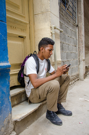 stoop: HAVANA - CUBA JUNE 19, 2016: A young man checks his cell phone for messages while sitting on the stoop of his home, one of thousands of deteriorating and decaying buildings in La Habana Vieja.