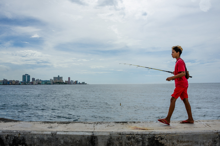 seawall: Havana, Cuba, June 20, 2016 - Boy with a fishing rod walks along the seawall of the Malecon of La Habana Vieja with the city skyline in the distance.