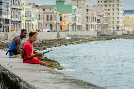 seawall: Havana, Cuba, June 20, 2016 - Boy and young man fish from the seawall of the Malecon with historic homes of the city behind them.