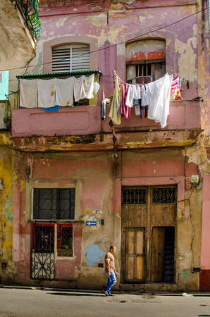 man laundry: Havana, Cuba, June 19, 2016 - A man walks along the street where laundry is hung outside of deteriorating and decaying homes in the historic La Habana Vieja neighborhood. Editorial