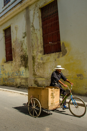vieja: Havana, Cuba, June 19, 2016 - A man rides a bicycle with a large card box to transport goods along a street in the La Habana Vieja neighborhood.