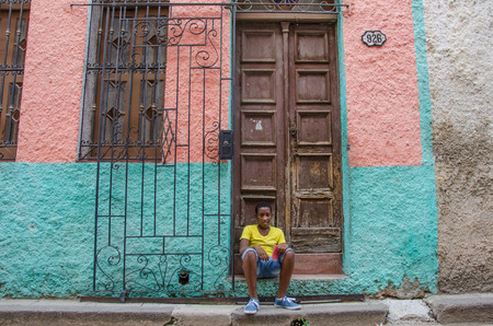 vieja: Havana, Cuba June 19, 2016 - Cuban boy sits on the steps of his house La Habana Vieja recently painted in bright pink and turquoise colors. Editorial