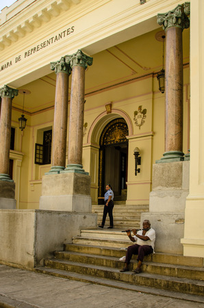 habana: Havana, Cuba June 19, 2016 - An old man, sitting on the steps of a historic building in La Habana Vieja, plays a flute to supplement his meager pension from the Cuban government.