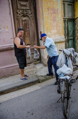 habana: Havana, Cuba June 19, 2016 - An old man on a bicycle delivers newspapers to a resident of one of thousands of deteriorating and decaying buildings in La Habana Vieja. Editorial