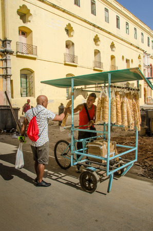 vieja: Havana, Cuba June 19, 2016 - Man sells biscuits from his bicycle to a male customer in the historic La Habana Vieja neighborhood.
