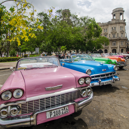 vieja: Havana, Cuba, June 17, 2016 - Colorful classic convertible cars popular with tourists are parked near the Museum of Fine Arts in La Habana Vieja waiting for passengers. There are thousands of restored classic cars in Havana that were purchased prior to th Editorial