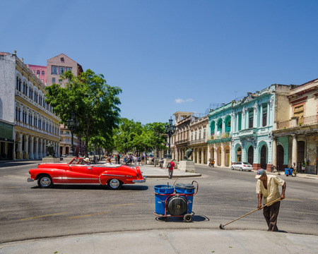 habana: Havana, Cuba, June 12, 2016 - Cuban sanitation worker sweeps the street known as Paseo de Marti as a red convertible  classic car passes by in the historic La Habana Vieja neighborhood.
