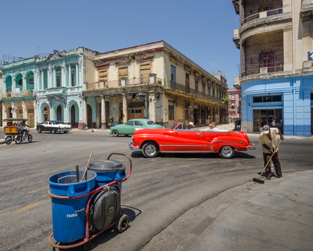 sweeps: Havana, Cuba, June 12, 2016 - Cuban sanitation worker sweeps the street known as Paseo de Marti as a red convertible  classic car passes by in the historic La Habana Vieja neighborhood.