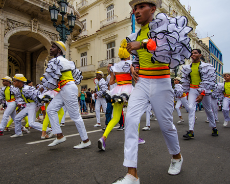 paseo: HAVANA - CUBA, JUNE 9, 2016: Male dancers in colorful costumes celebrate Havana Day with a parade along Paseo de Marti in the historic La Habana Vieja neighborhood.