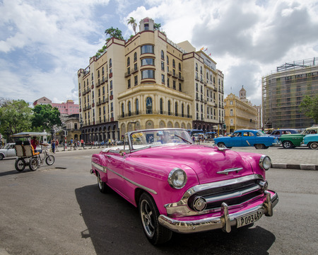 restored: HAVANA - CUBA. JUNE 10, 2016: Close-up of a hot pink restored classic convertible drives along Paseo de Marti with the Parque Central Hotel and the historic Plaza Hotel in the background.