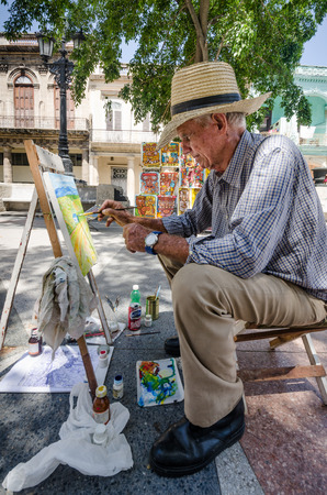 habana: Havana, Cuba, June 12, 2016: Cuban male is one of many artists and others selling crafts Sunday afternoons on the beautiful boulevard Paseo di Marti in the historic La Habana Vieja neighborhood. Editorial