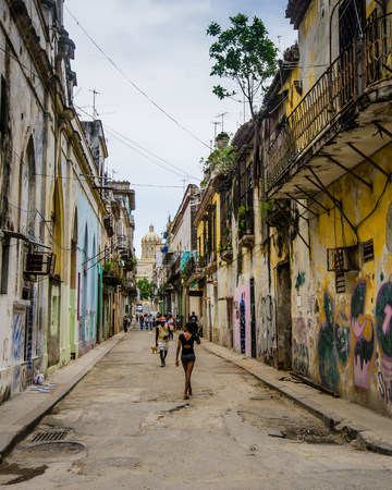 Havana, Cuba, June 20, 2016: People walk along Cuarteles, a residential street with graffiti on some of the deteriorating buildings. The dome of the Museum of the Revolution can be seen in the distance.