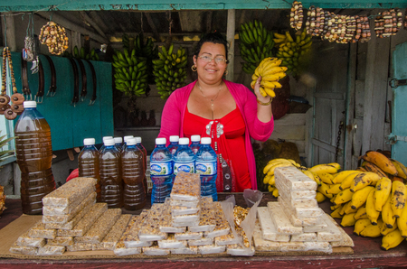roadside stand: Topes de Collantes, Cuba,  June 15, 2016: Smiling Cuban woman sells bananas, snacks and water at a roadside stand in this resort community in the mountains of Central Cuba.
