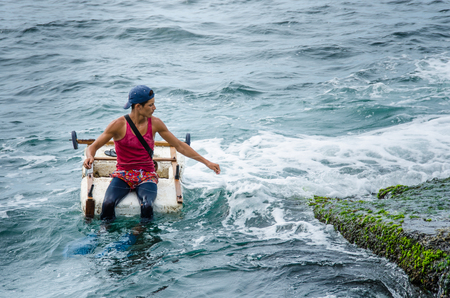 Havana, Cuba, June 20, 2016 : Young man fishes from a home-made raft a short distance from the seawall of the Malecon in Havana harbor.