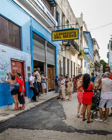 vieja: HAVANA – CUBA, JUNE 20, 2016: A couple autograph the wall outside of one of Hemingway's favorite bars, the legendary La Bodeguita del Medio on the Emperado in the La Habana Vieja neighborhood.