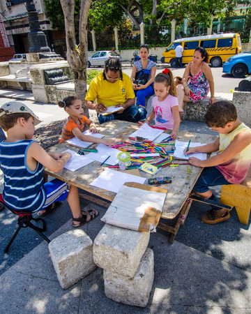 paseo: HAVANA - CUBA JUNE 12, 2016: A table has been set up for Cuban children to draw and color on a Sunday afternoon on the Paseo de Marti boulevard in the historic La Habana Vieja neighborhood.