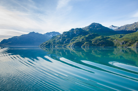 alaska scenic: Cruise ship sailing in Southeast Alaska creates ripples across the calm waters of the inside passage.