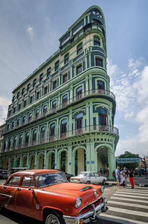 Havana, Cuba,  June 10, 2016 - Classic car drives by the restored luxury Saratoga Hotel, built in 1879, an excellent example of colonial architecture in the La Habana Vieja neighborhood.