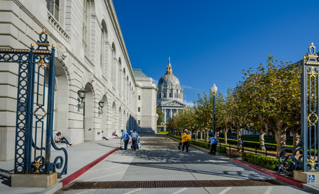 San Francisco, United States, November 29, 2016 - Sanitation workers clean the walkway of Memorial Court between the War Memorial Opera House and the Veterans Building with the City Hall in the background.