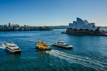 Sidney, Australia, November 2, 2016 - Passenger ferries pass in front of the Sidney Opera House, a multi-venue performing arts center, designed by Danish architect Jorn Utzon.