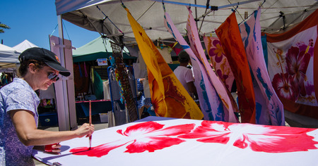 collectivity: Noumea, New Caledonia, October 27, 2016 - A female artist paints lush flowers on fabrics for sale at the popular outdoor market in the capital city of the special collectivity of France  in the southwest Pacific Ocean.