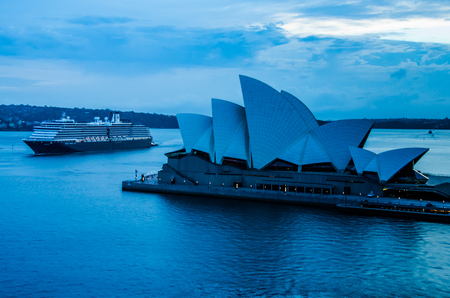 Sidney, Australia, December 21, 2017 - Cruise ship passes the iconic Sidney Opera House in the early morning hours as it enters the harbor. The multi-venue performing arts center was designed by Danish architect Jorn Utzon.