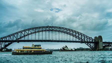 Sidney, Australia, December 21, 2017 - Passenger ferry passes in front of the Sidney Harbour Bridge with the iconic Sidney Opera House in the distance.