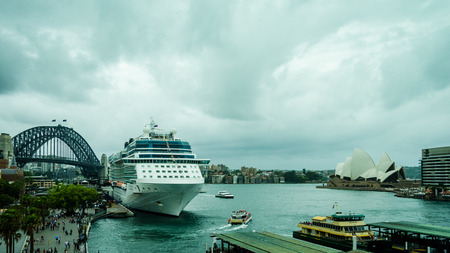 Sidney, Australia, December 21, 2017 - A cruise ship has docked at the ferry terminal beside the iconic Sidney Opera House with the world's tallest steel arch bridge in the distance.