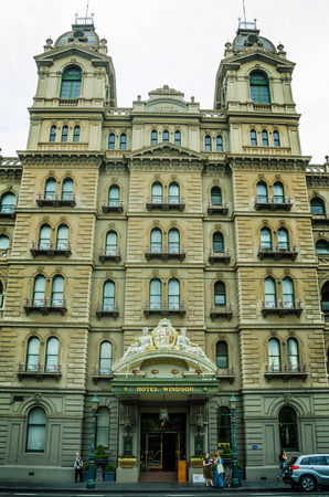 Melbourne, Australia, December 19, 2017 - Woman waits for a cab in front of the historic Hotel Windsor, known for its old-world charm and unparalleled luxury, is the last remaining grand hotel from the Victorian era. and continues to play an integral role
