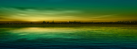 sunrise ocean: abstract nature green background with panorama of city and sunset