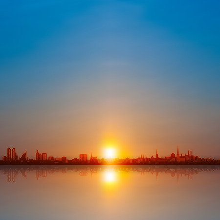 horizon reflection: abstract background with spring sunset and silhouette of city