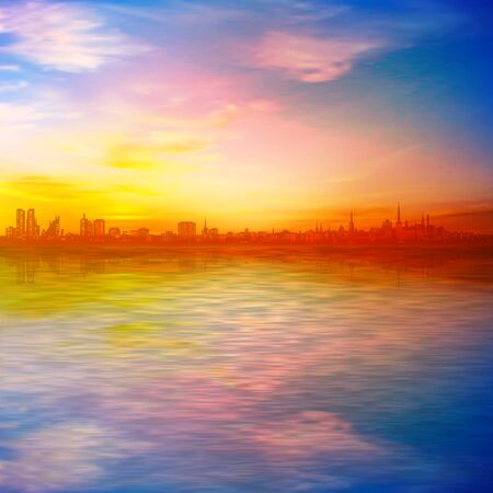 abstract spring background with gold sunset pink sky and silhouette of city