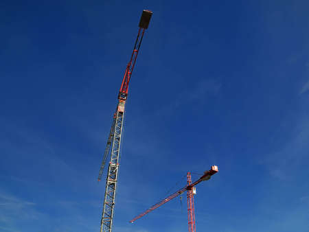 Two cranes against blue sky