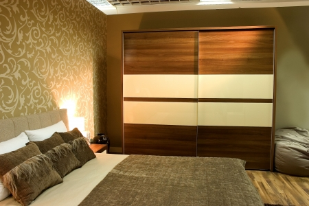 bedroom interior: Modern bedroom with brown wardrobe and bed with two pillows.