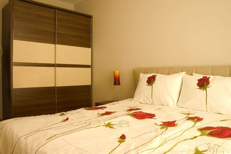 Warm bedroom with wardrobe and large bed with pillows and roses sheets.