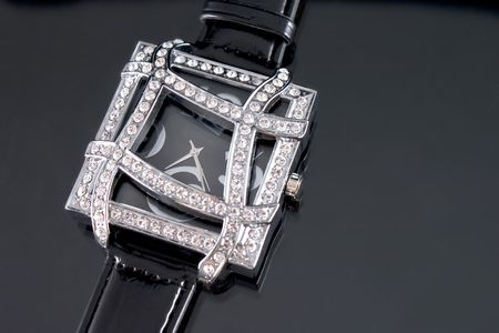 Woman luxury watch in silver tone with crystals on black background.