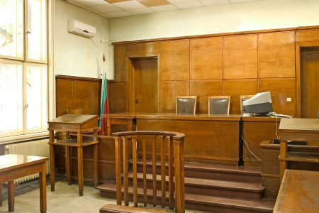 Old vintage wooden court room with judge chairs and a witness stand.
