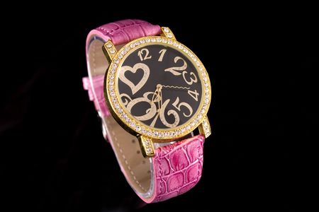 Woman luxury watch in gold tone with crystals on black background.