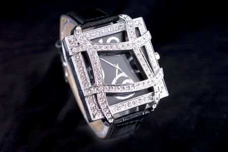 stell: Woman luxury watch in silver tone with crystals on black background.