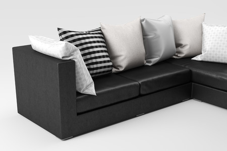 Closeup of black leather sofa with pillows isolated on white background.
