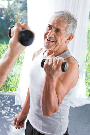 assisting: Senior man doing sport Stock Photo