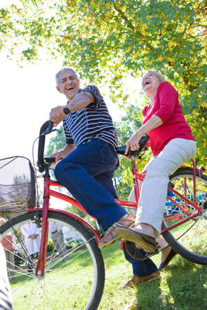 tandem bicycle: Senior couple riding bicycle Stock Photo