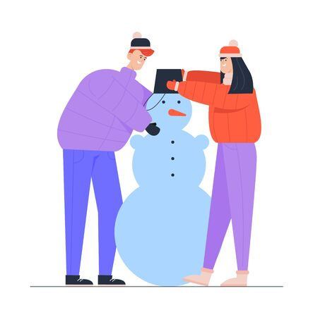 Young Man and Woman Wearing Warm Clothing Making Funny Snowman Put Bucket on his Head. Winter Time Outdoor Activity