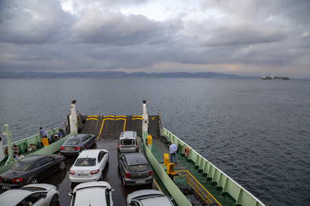 view in front of ferryboat, ferry approaching to port, people and cars waiting, weather is cloudly. Editorial
