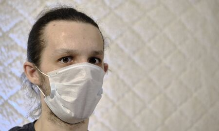 a man in a medical mask on a white background coronavirus color