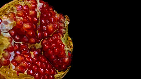 Closeup view of grain red grenades. Juicy ripe red pomegranates or pomegranates. Fruits of red ripe pomegranate on a studio background. Vegetarian concept, organic vitamins.